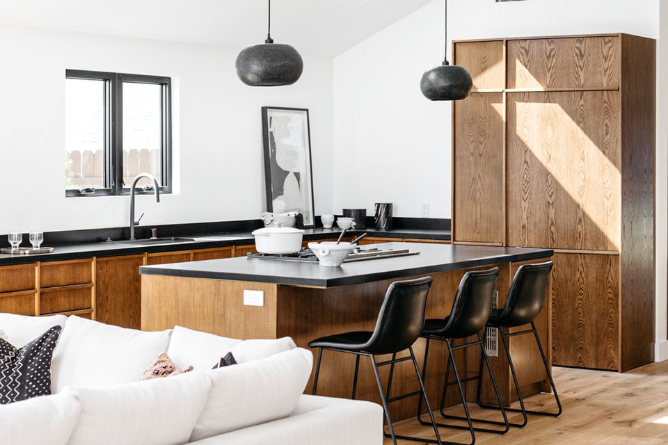 Kitchen with black soapstone countertops and wooden cabinets surrounded by white walls
