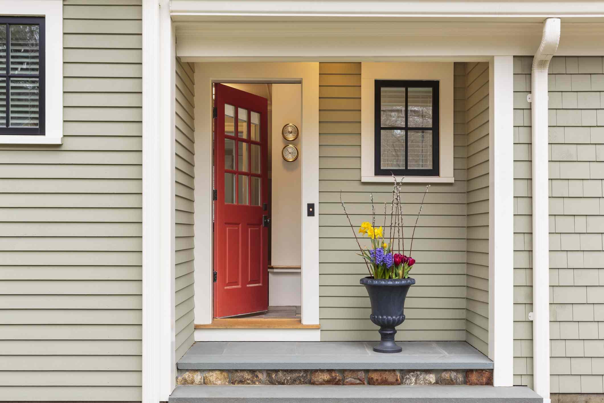entrada acogedora a una casa con puerta roja y flores