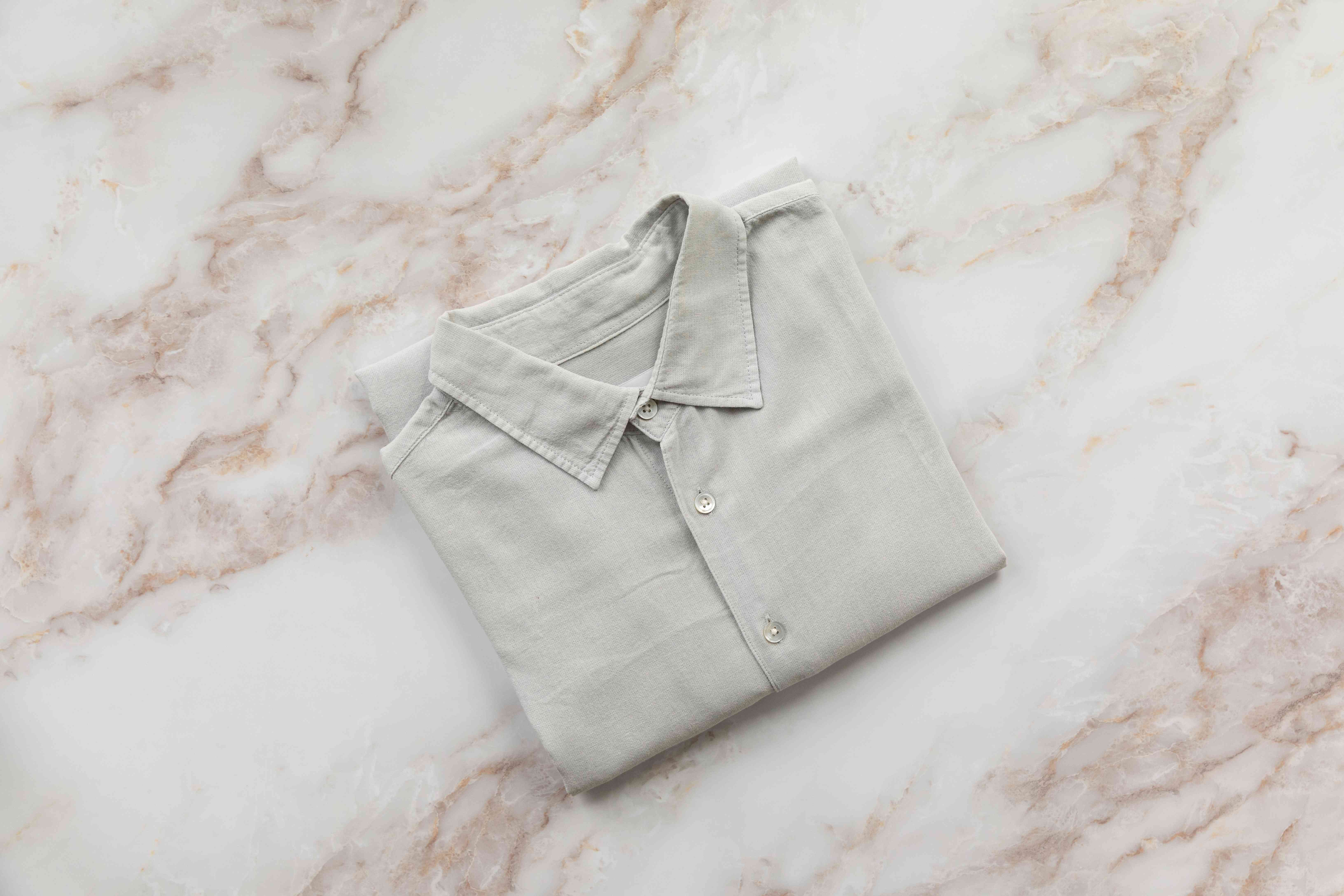 Tan collared shirt folded neatly face up on white marbled surface