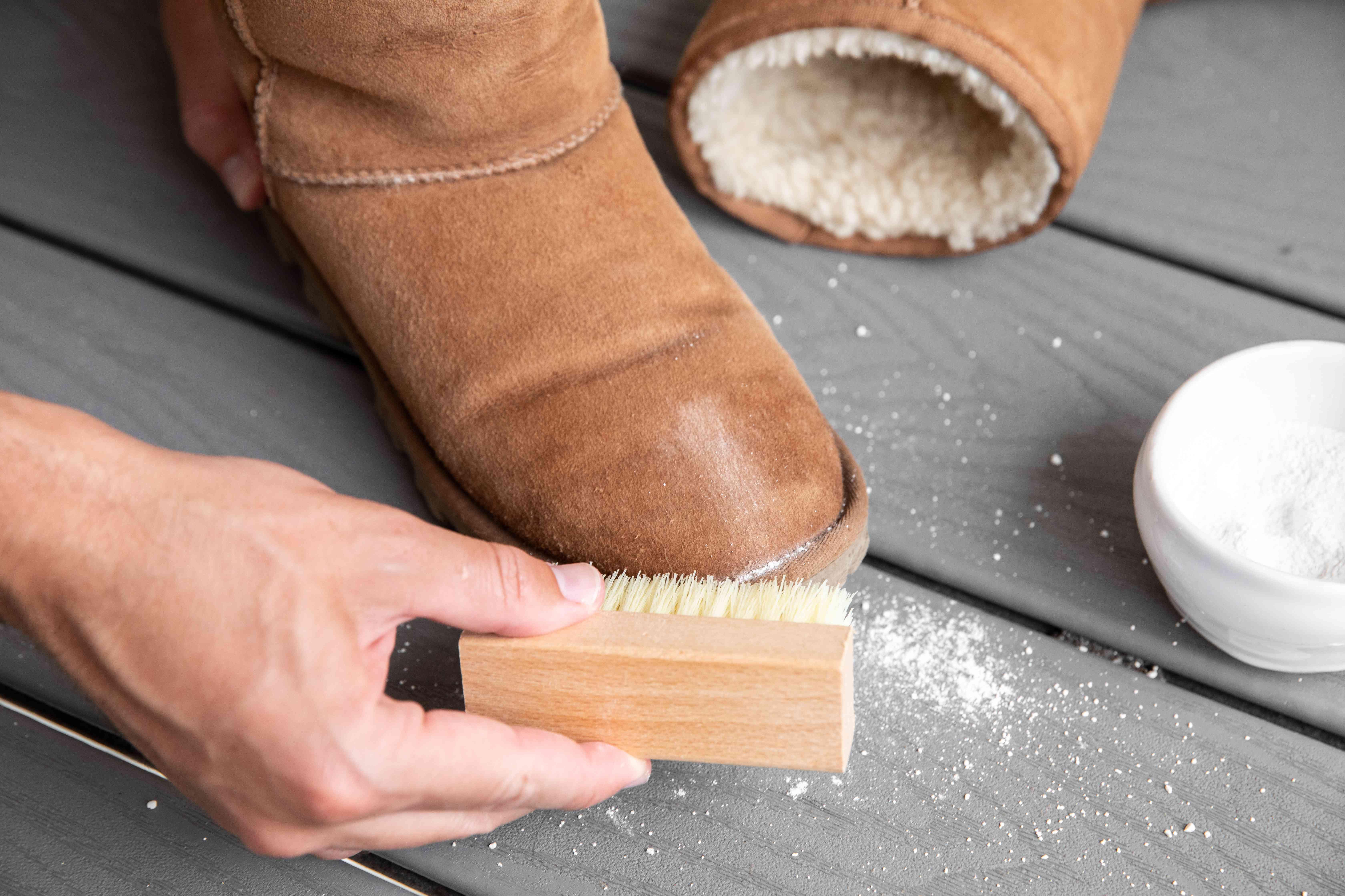 Someone brushing baby powder off an Ugg boot