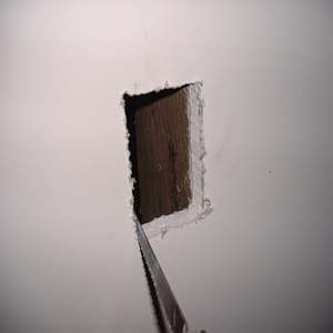 A photo of cutting a hole in drywall.