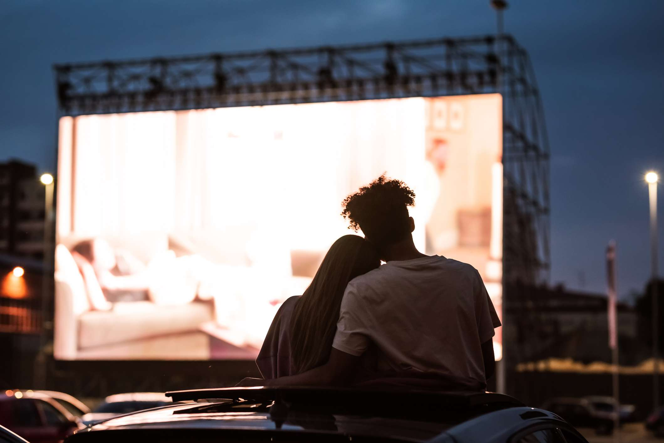 Silhouetted view of attractive young couple, boy and girl embracing at a drive in movie