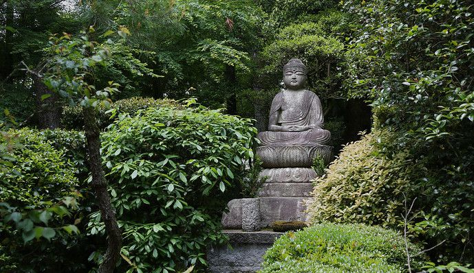 Stone Buddha statue surrounded by green leafy shrubs and trees in a park