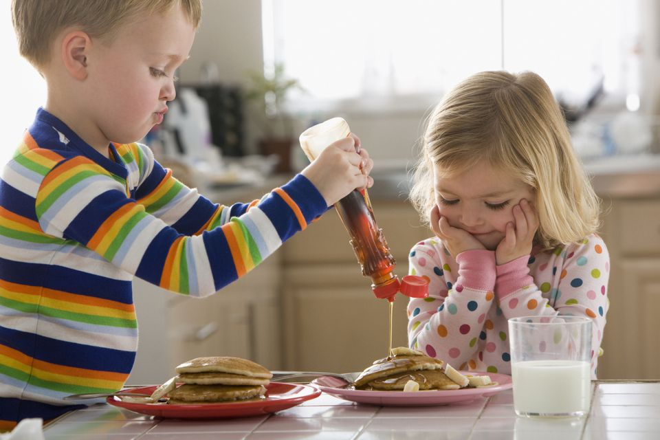 Boy pouring syrup on sister's pancakes.