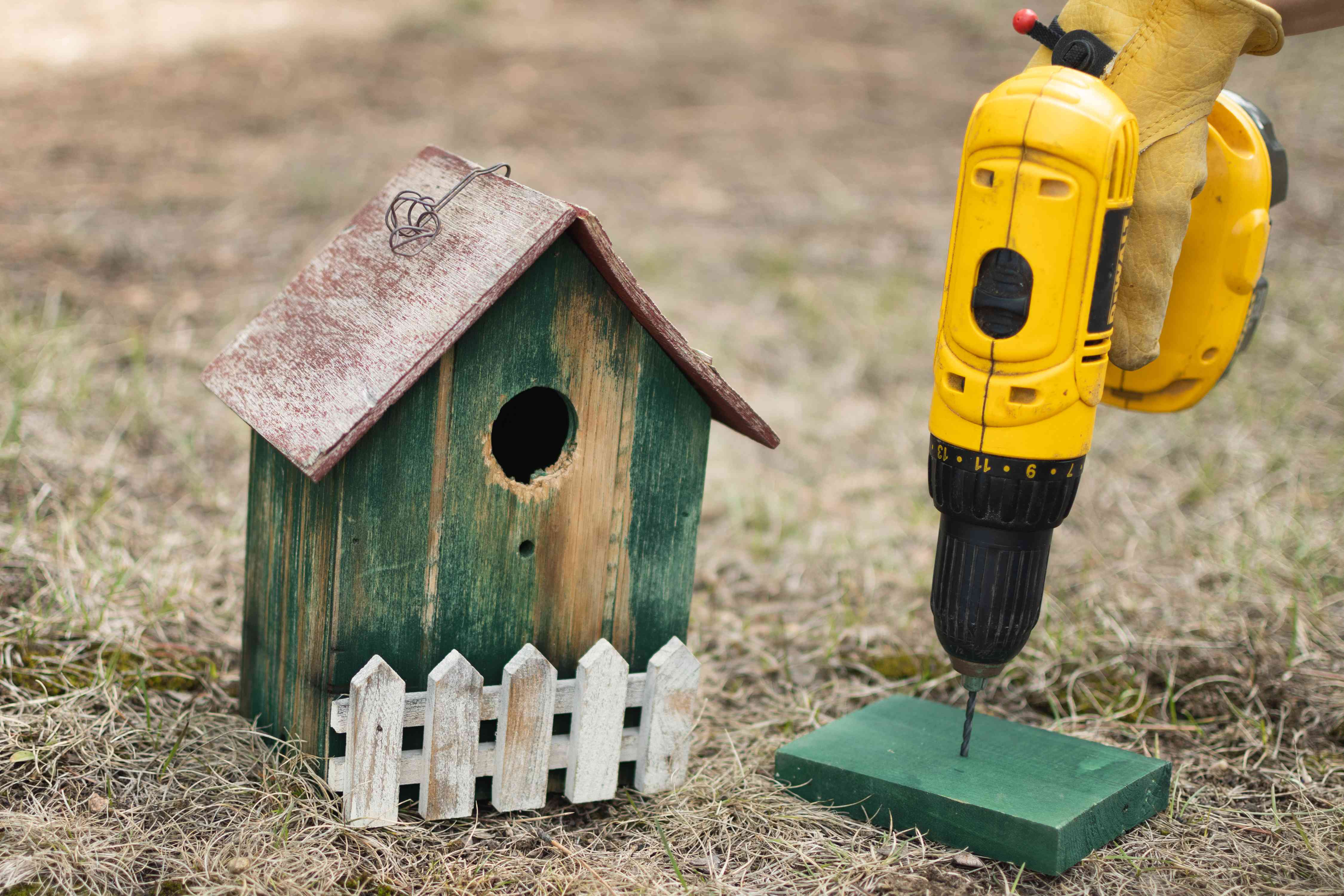 Wooden green birdhouse bottom secured with yellow electric drill