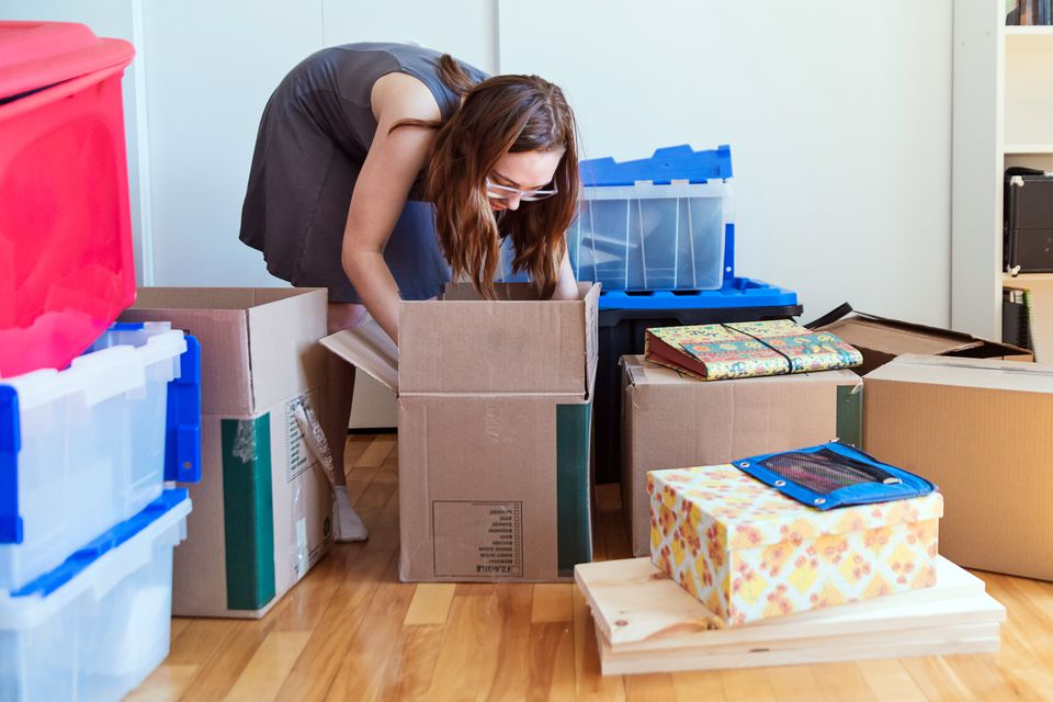 A woman packing her apartment into many boxes