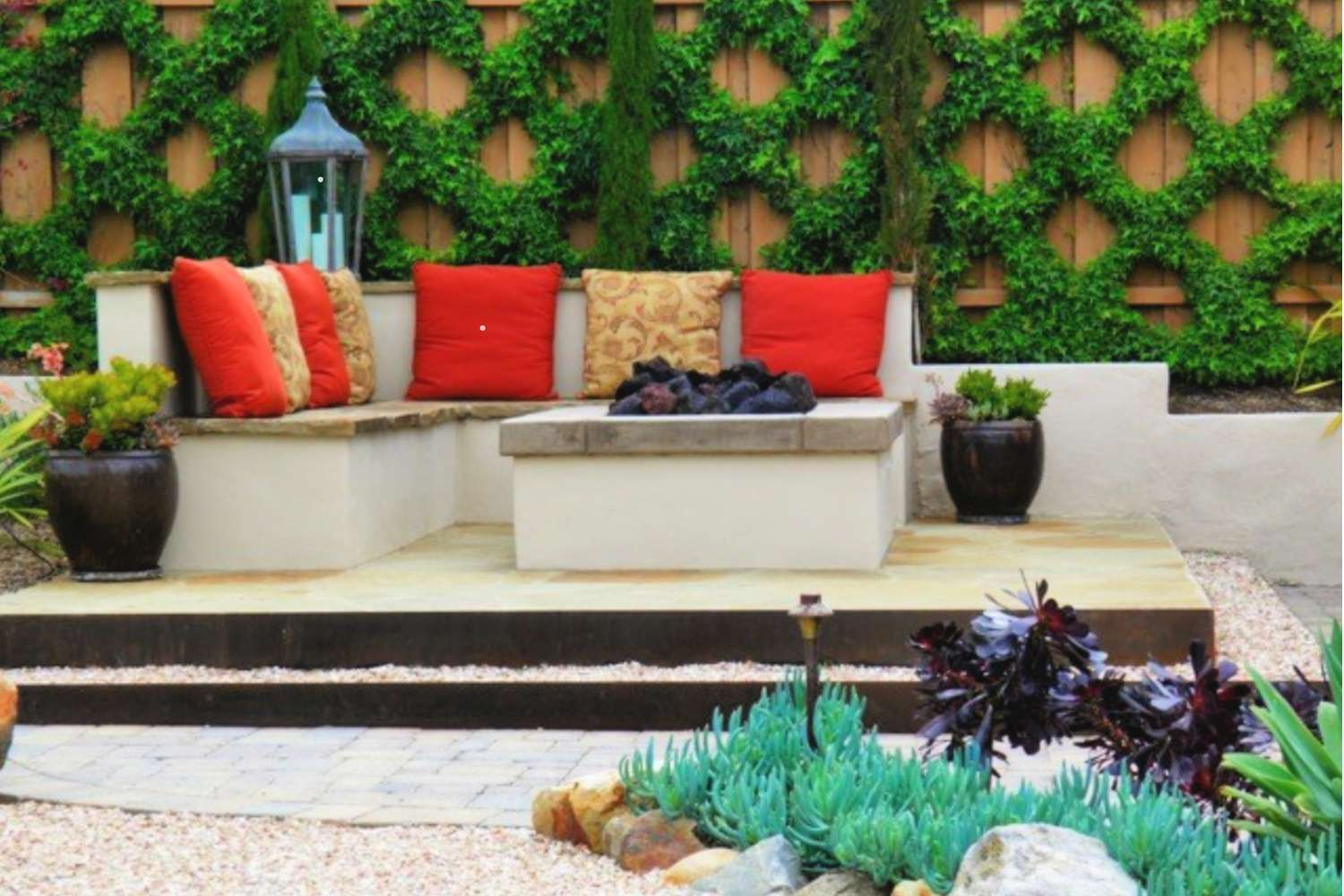Vertical garden is a diagonal pattern near a patio with furniture and pillows.