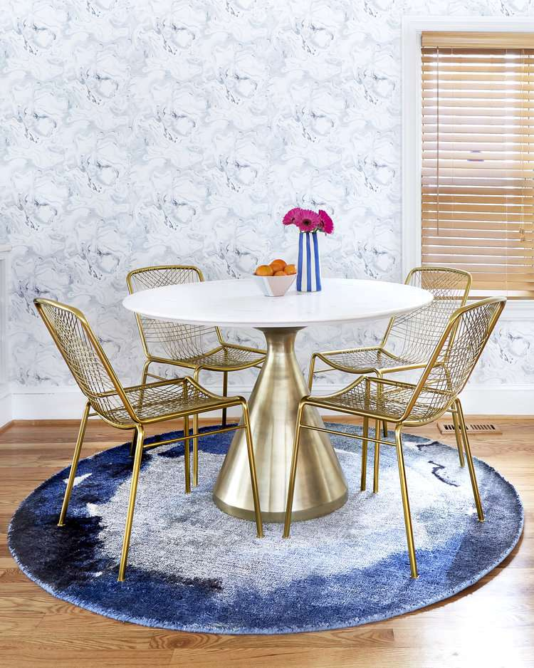 brass round table and chairs in blue dining room