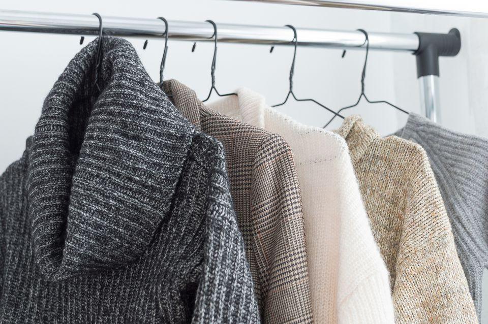 suéteres colgando de un estante