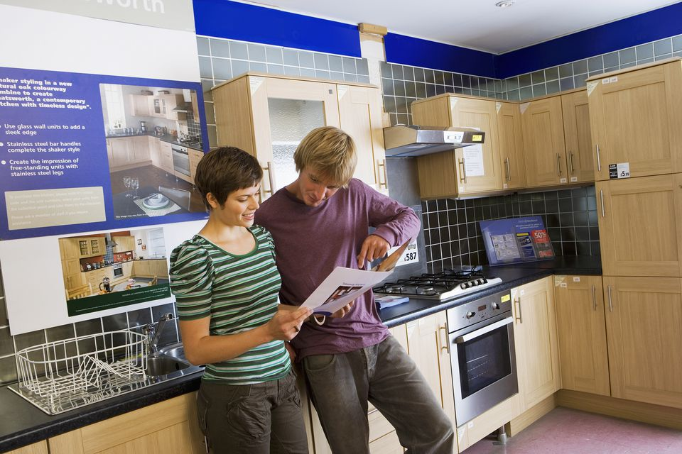 Couple shopping in kitchen section of home furnishings store, reading brochure, smiling