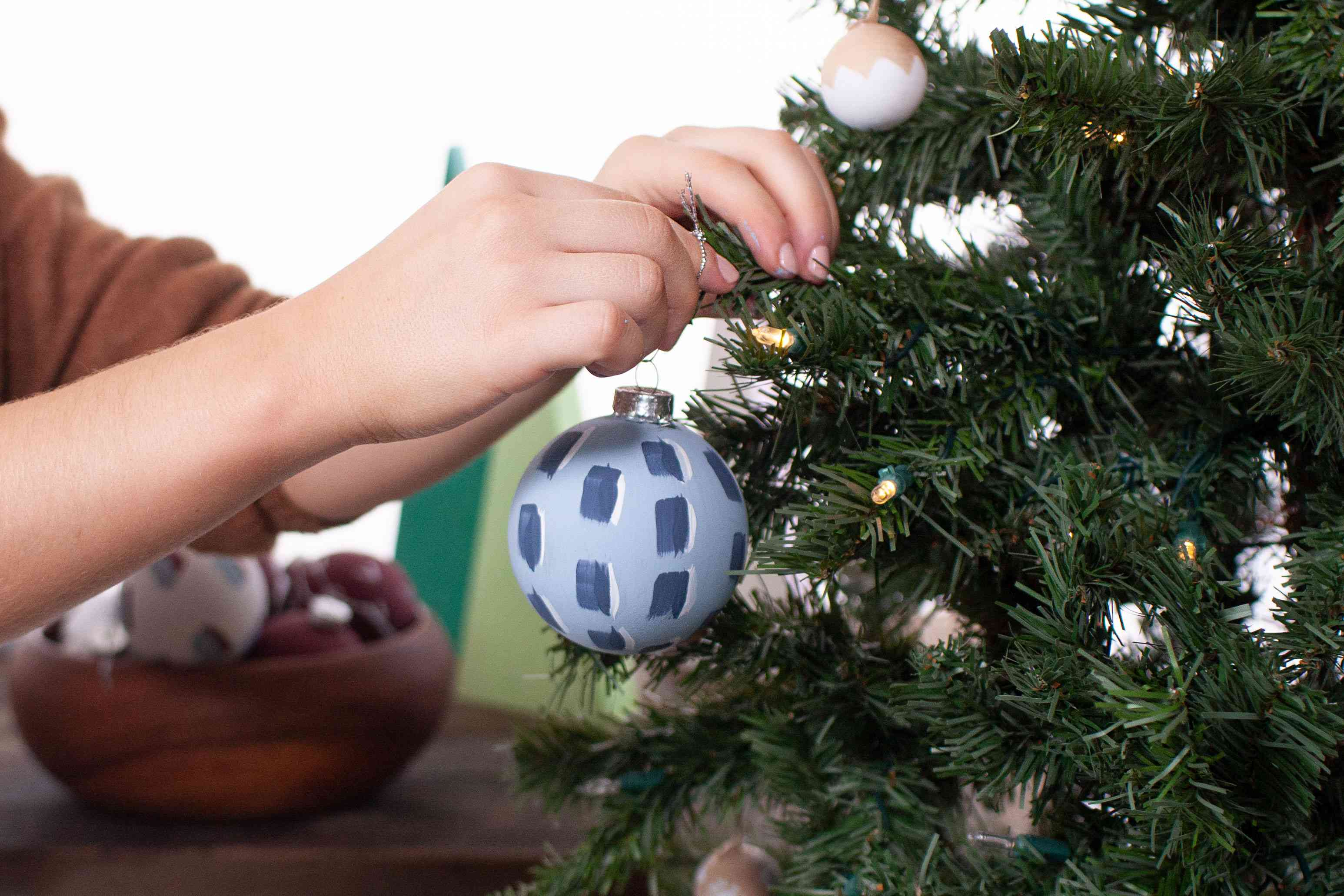 placing a painted ornament on the tree