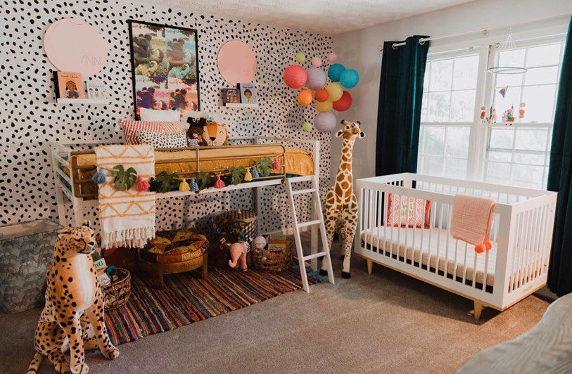 A combo kid's loft and nursery with wild stuffed animals and a polka dot accent wall.