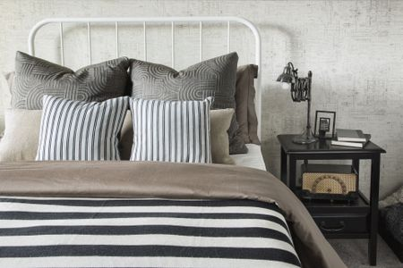 Striped And Patterned Pillows Blanket On Bed