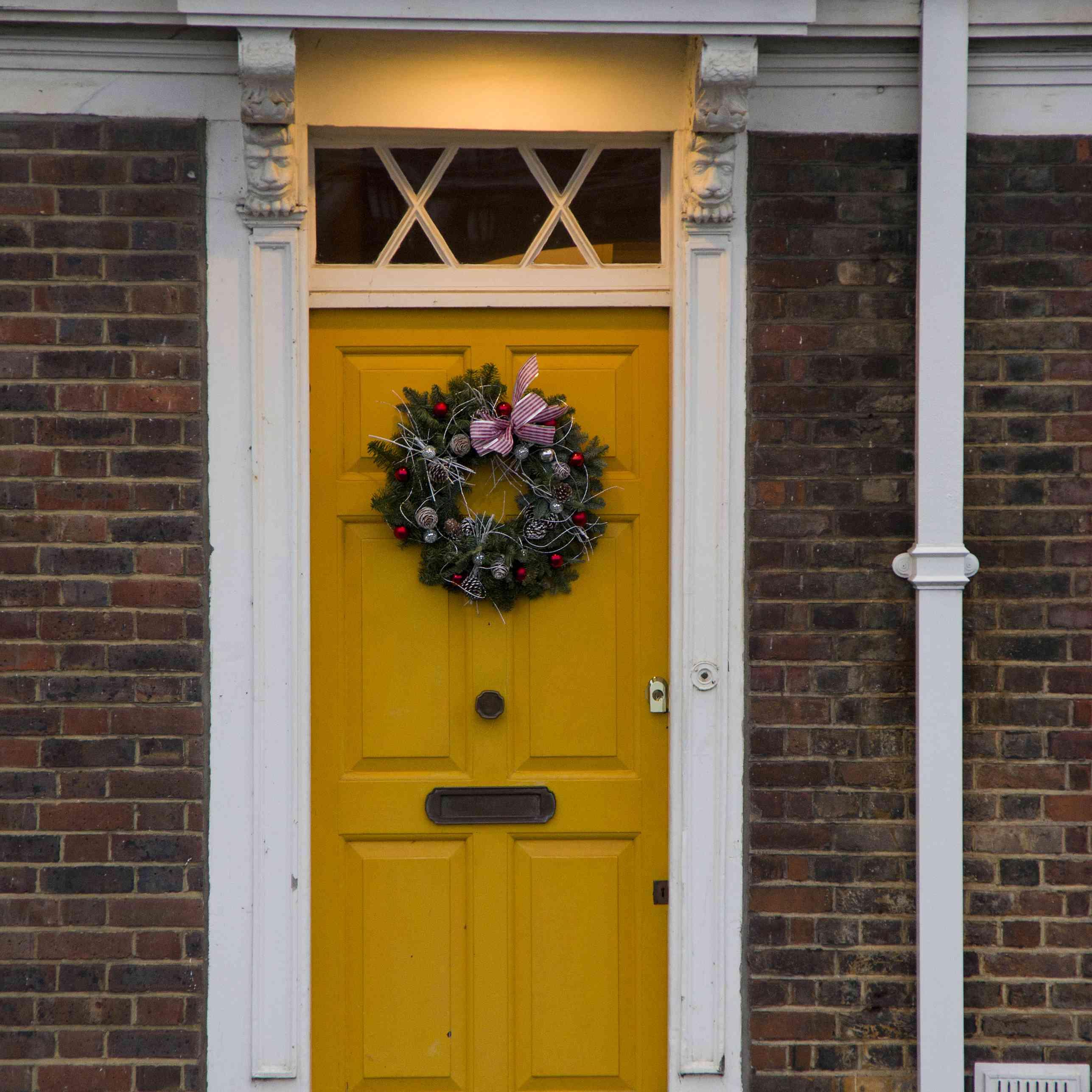 A warm orange-yellow door on a brick house with white trim