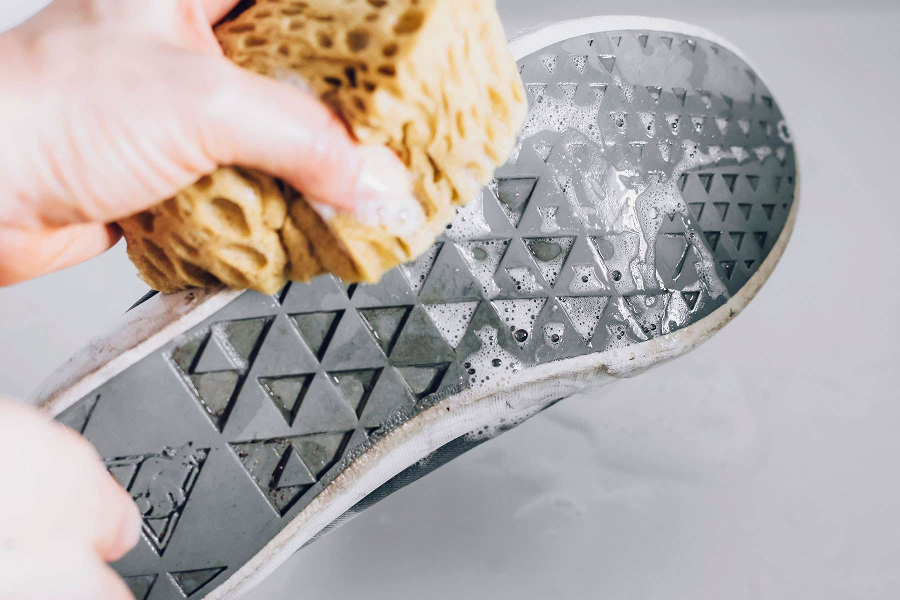 using a sponge to scrub the shoes