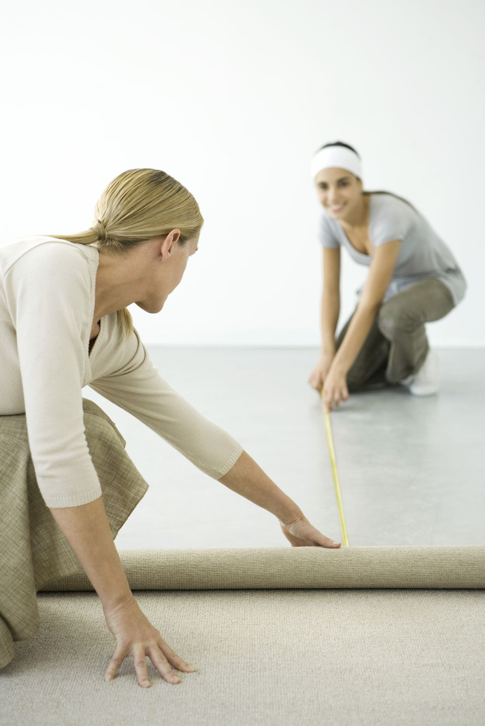 Two women measuring the floor for a carpet