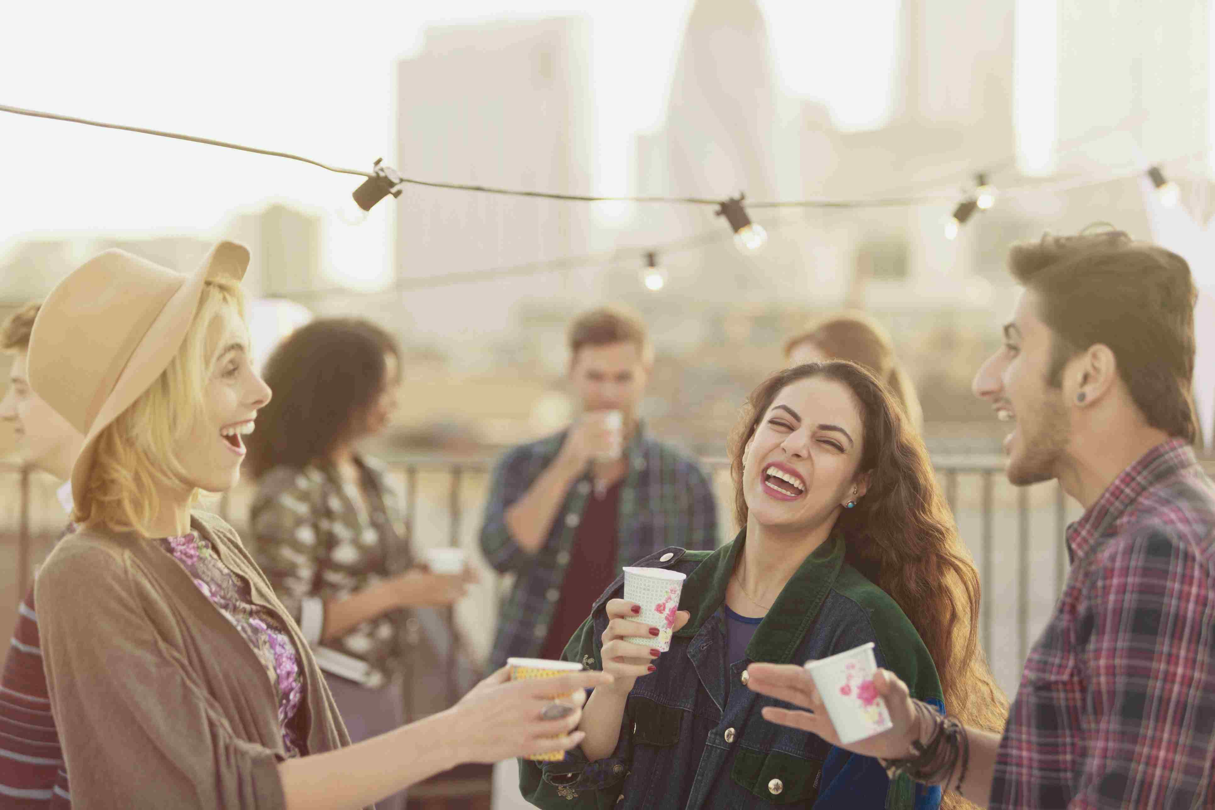 Young adult friends laughing and drinking at rooftop party