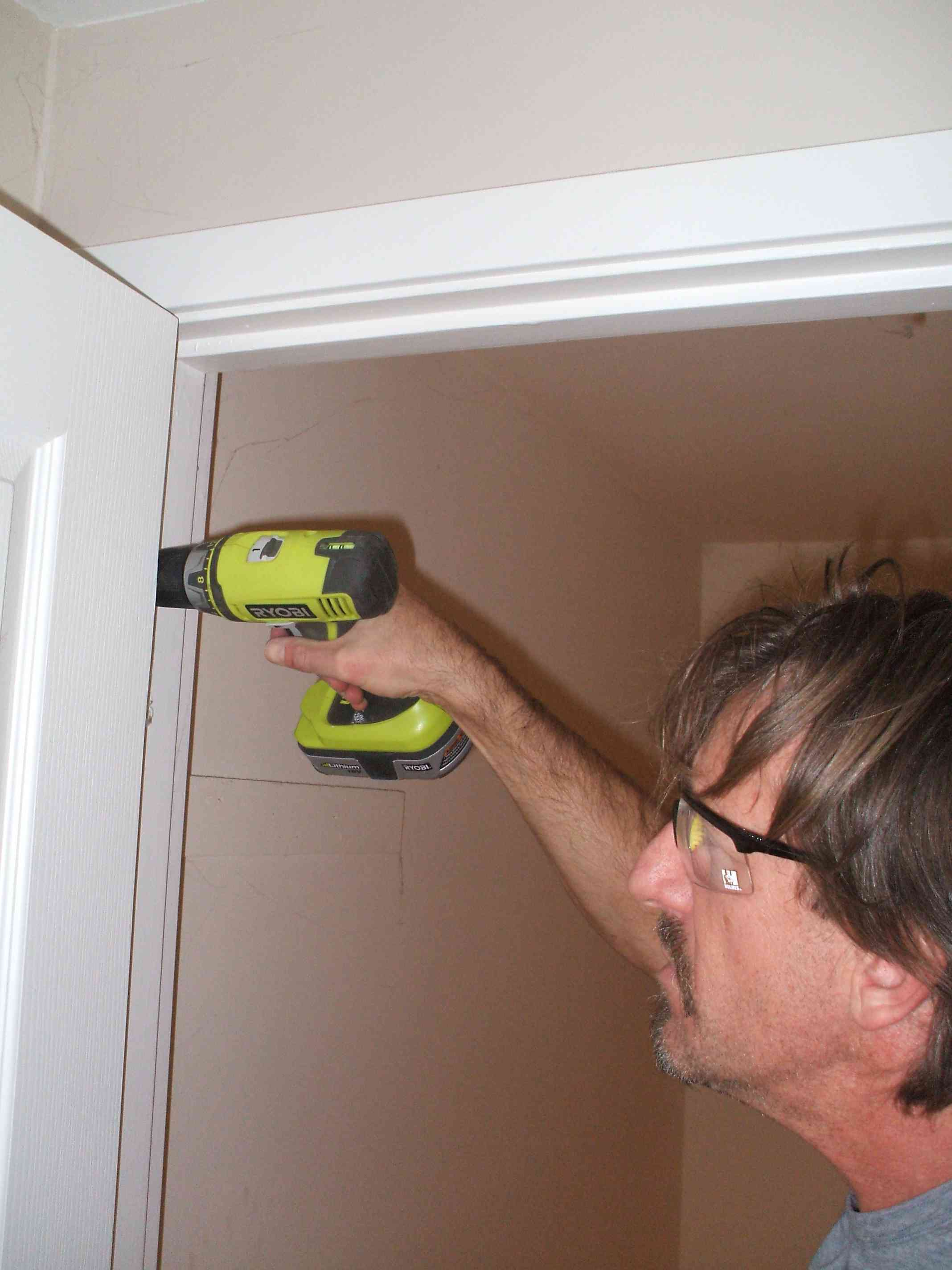 A man removing a door from its frame