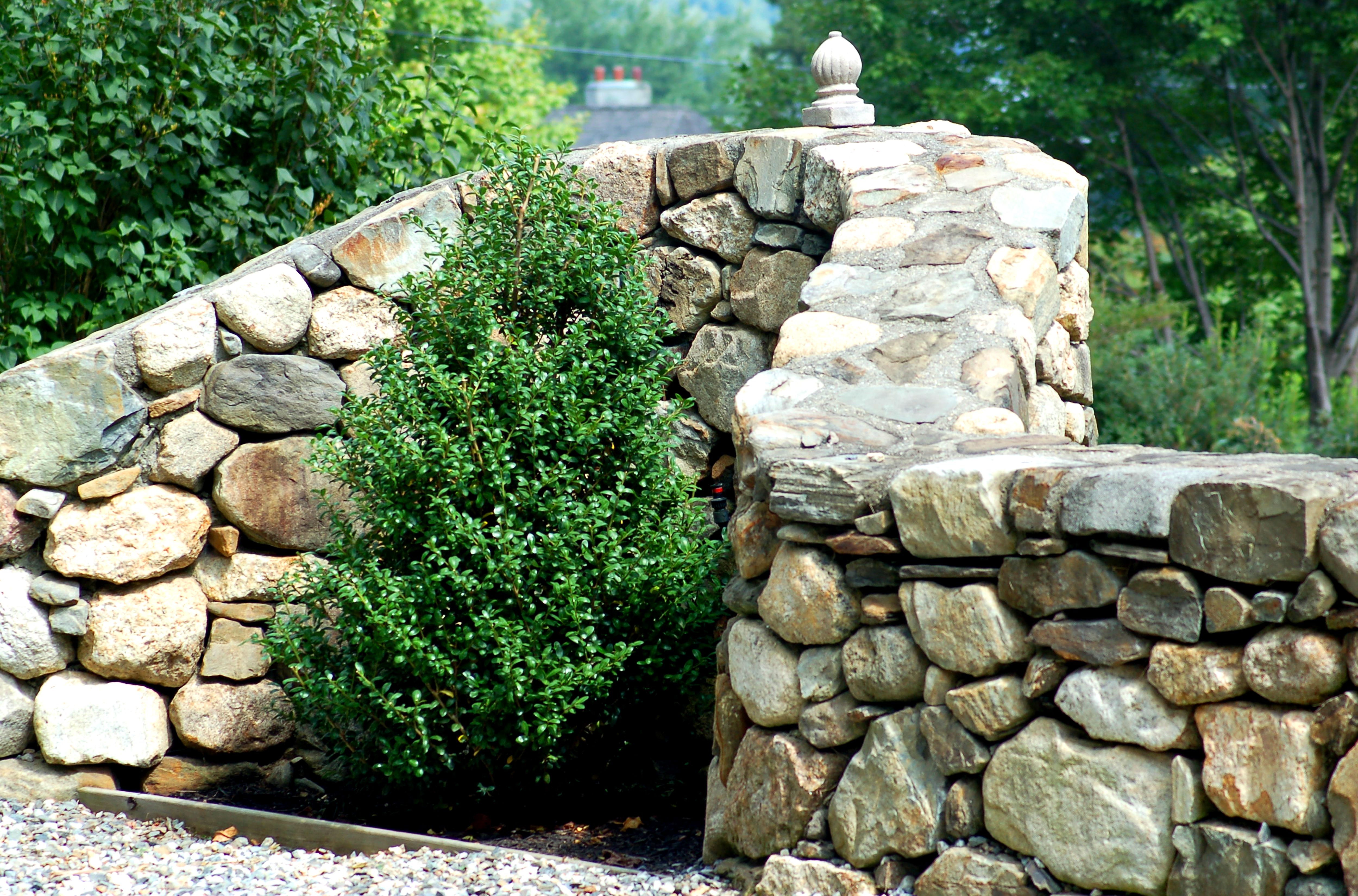 Insert a niche into your stone wall (image) to accommodate a shrub. The latter will soften the look.