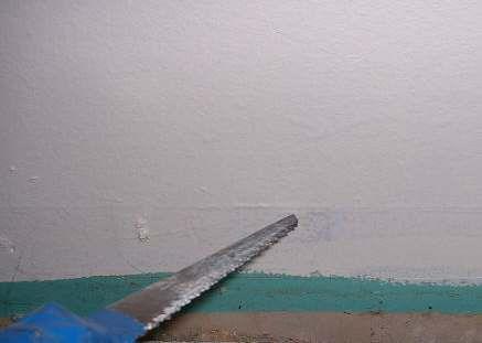 A photo of a drywall saw cutting drywall.