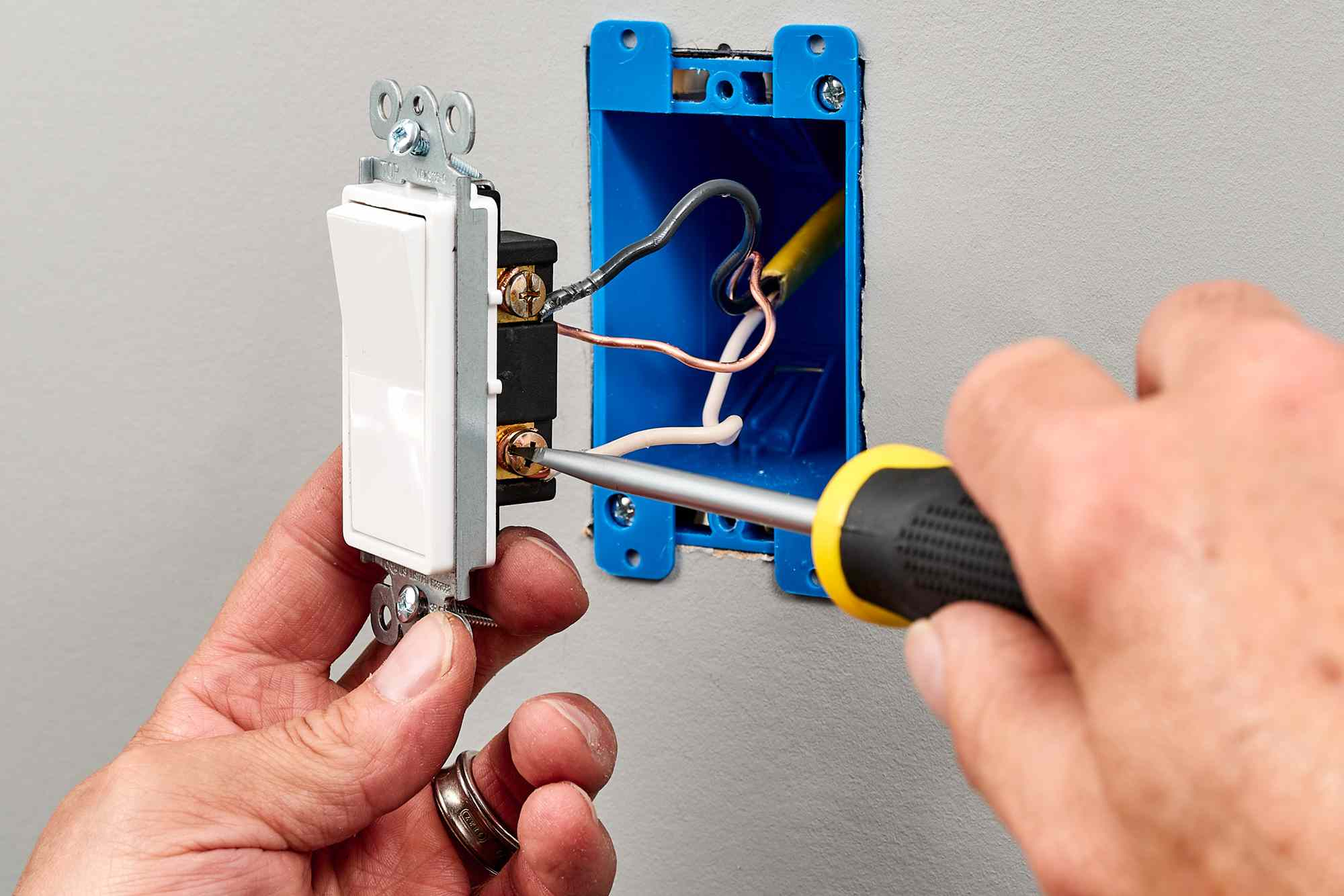 Ground and hot wires screwed into screw terminal of single-pole switch with screwdriver