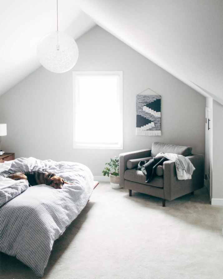 Remodeled attic space turned to master bedroom, with gray walls and dog laying on bed.