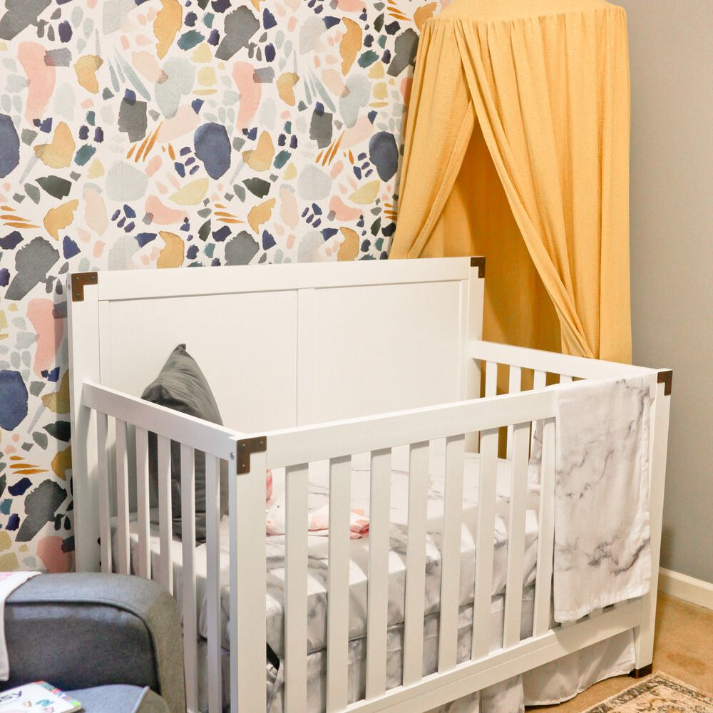 nursery with yellow, blue, olive green, and pink color scheme