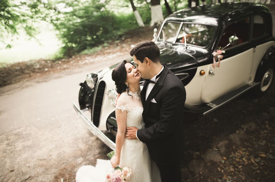 Newlywed couple kissing by car