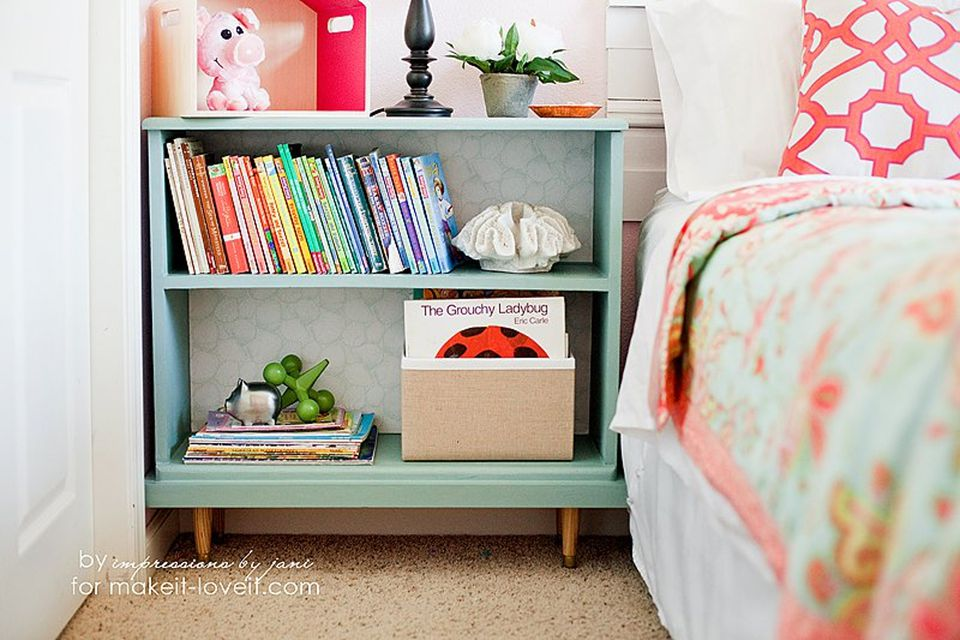 Short bookcase with legs repurposed as a nightstand with books and toys next to a bed.