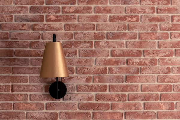 Stylish small golden lamp sconce installed on red brick wall closeup