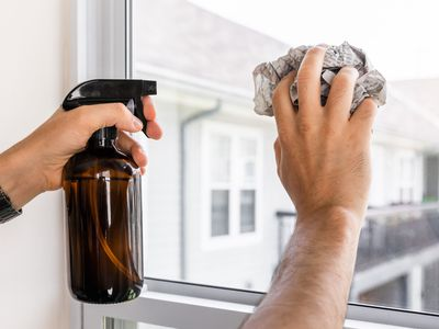 person using newspaper to clean a window