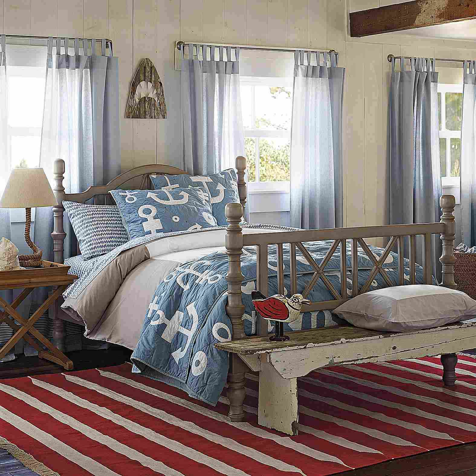 Habitación con alfombra roja y blanca a rayas y colcha azul náutica