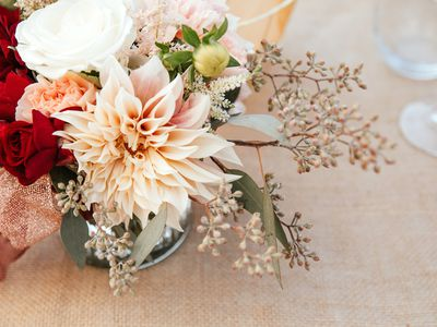 Rustic backyard wedding - reception tables with golden plates and chairs, dahlias, peonies and eucalyptus leaves and jute rope napkin rings.