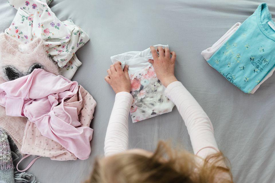 child folding laundry