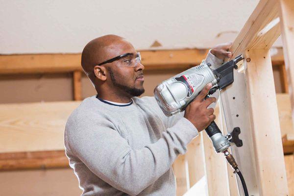 a construction worker holding a nail gun
