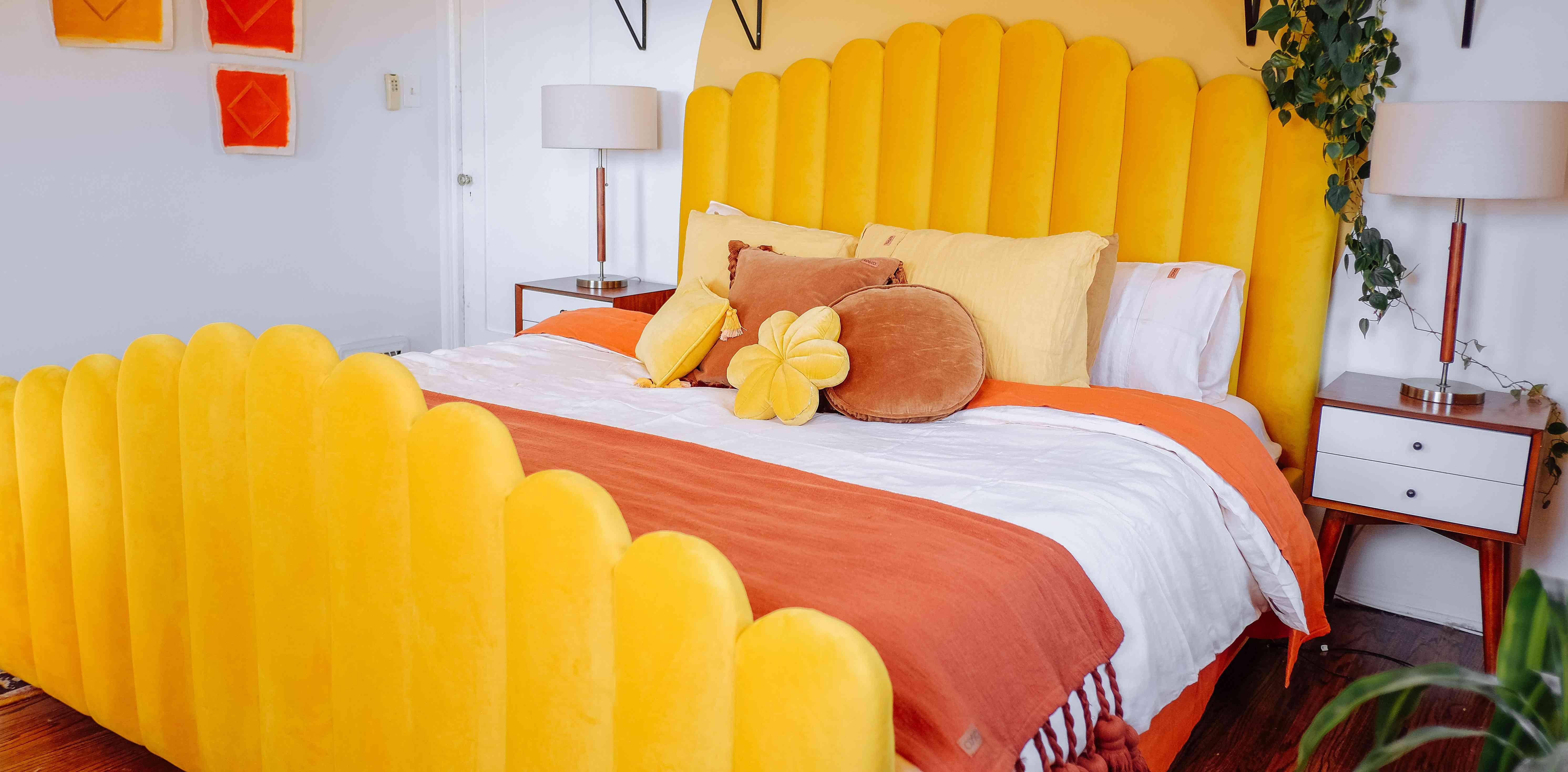 bedroom with plush yellow headboard, yellow mural, orange blankets