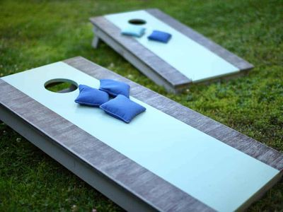 Blue and gray cornhole boards in a yard