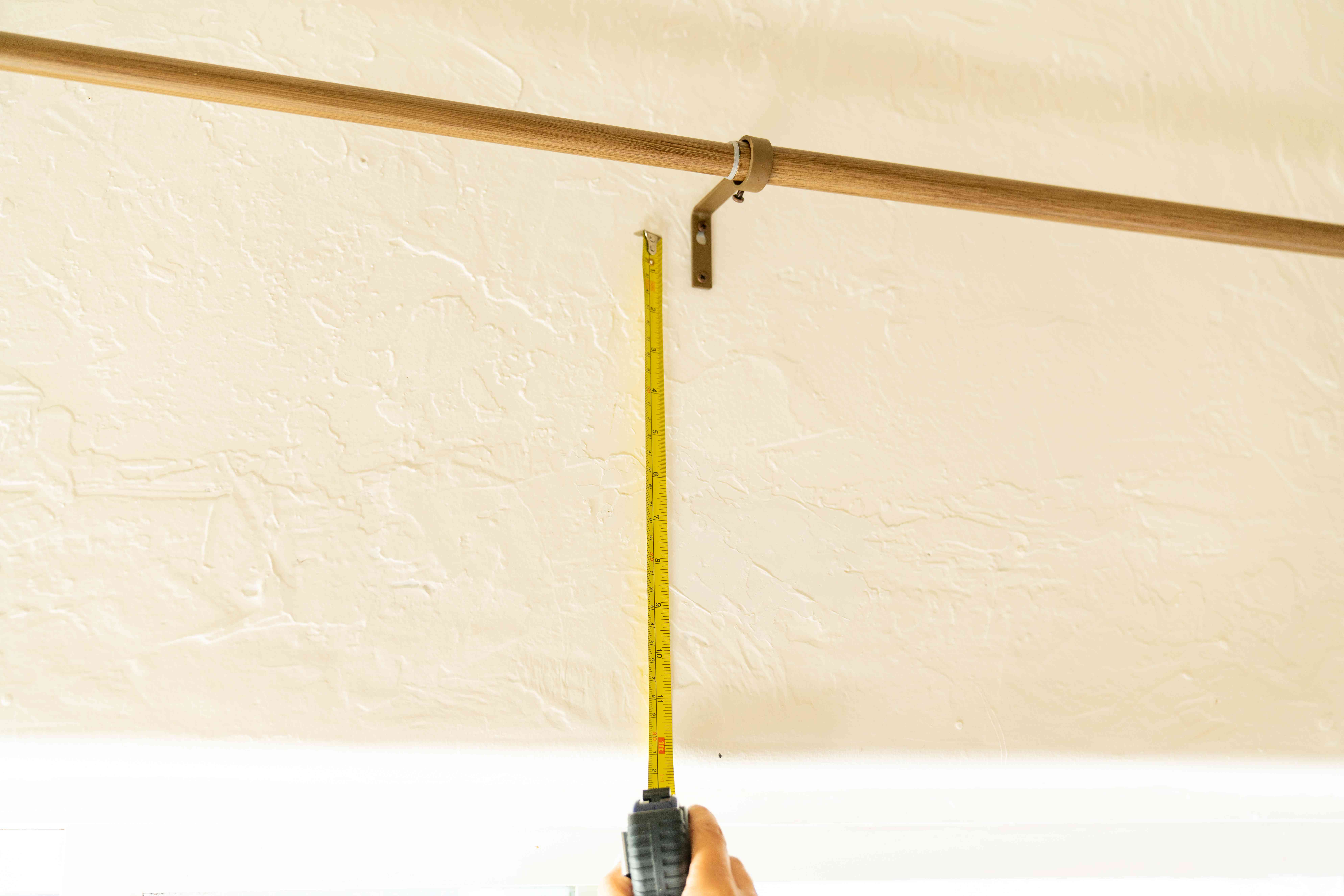 Curtain rod height measured above window with measuring tape