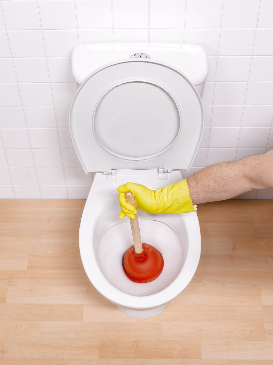 Man sticking toilet plunger in toilet bowl