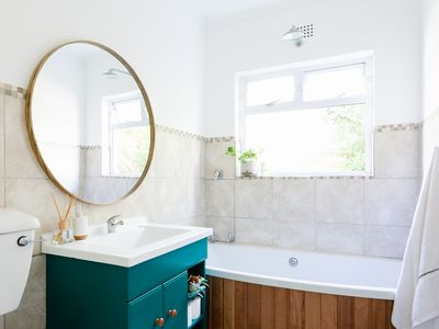Decorated guest bathroom with light-filled window, round mirror and teal colored bathroom cabinet