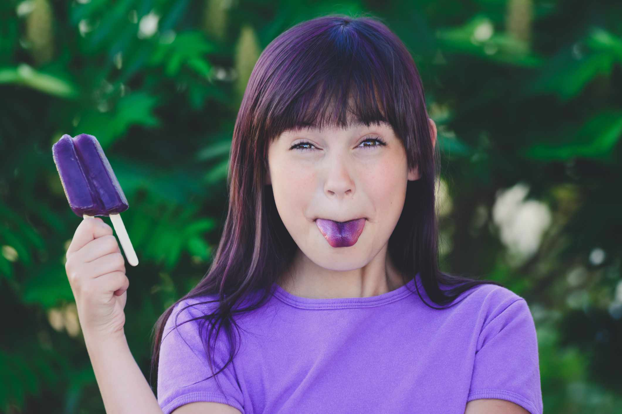 Young girl holding a purple popsicle with a purple tongue