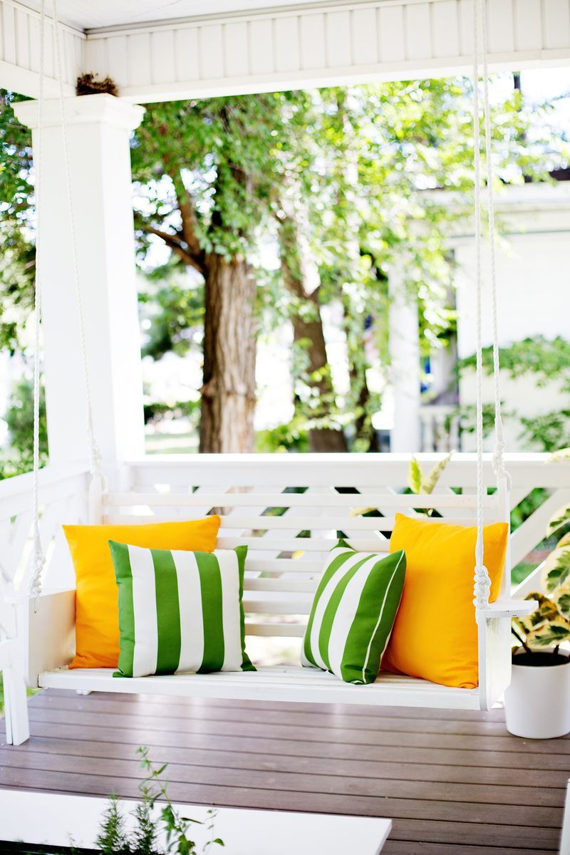 A photo of a with porch swing with green and yellow throw pillows