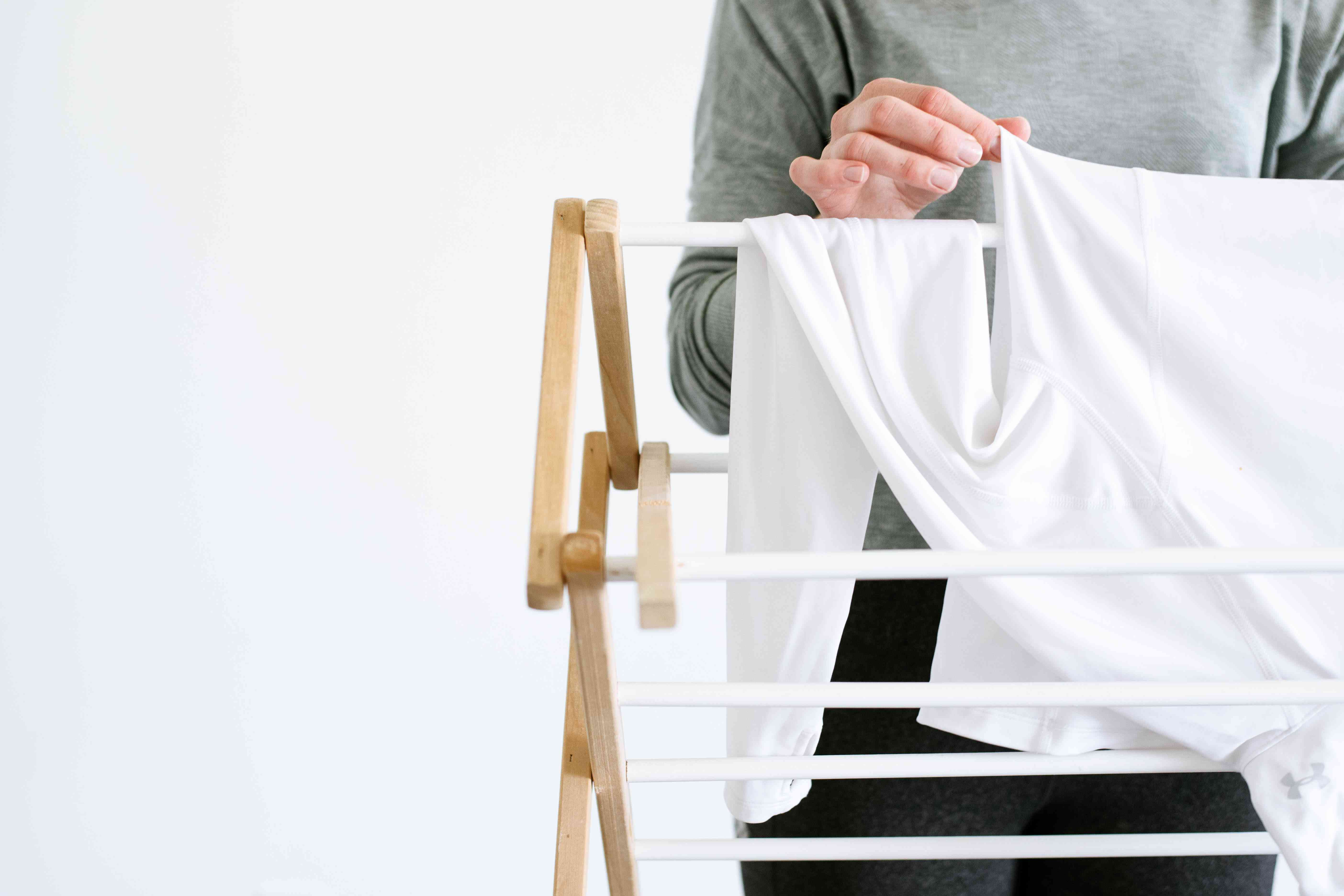Someone hanging a garment on a drying rack
