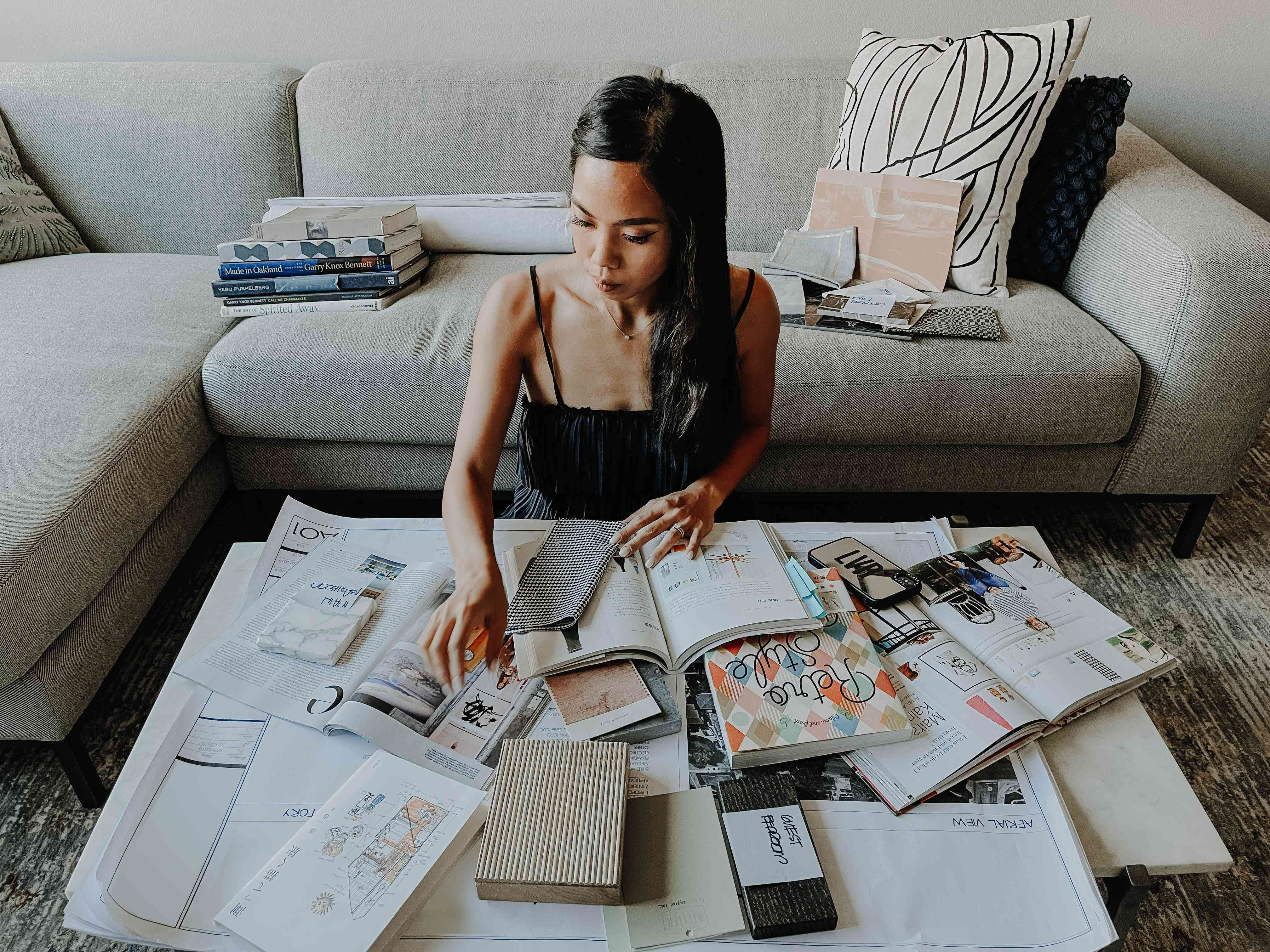 Lauren Reyes Lim poses with books and magazines next to a couch