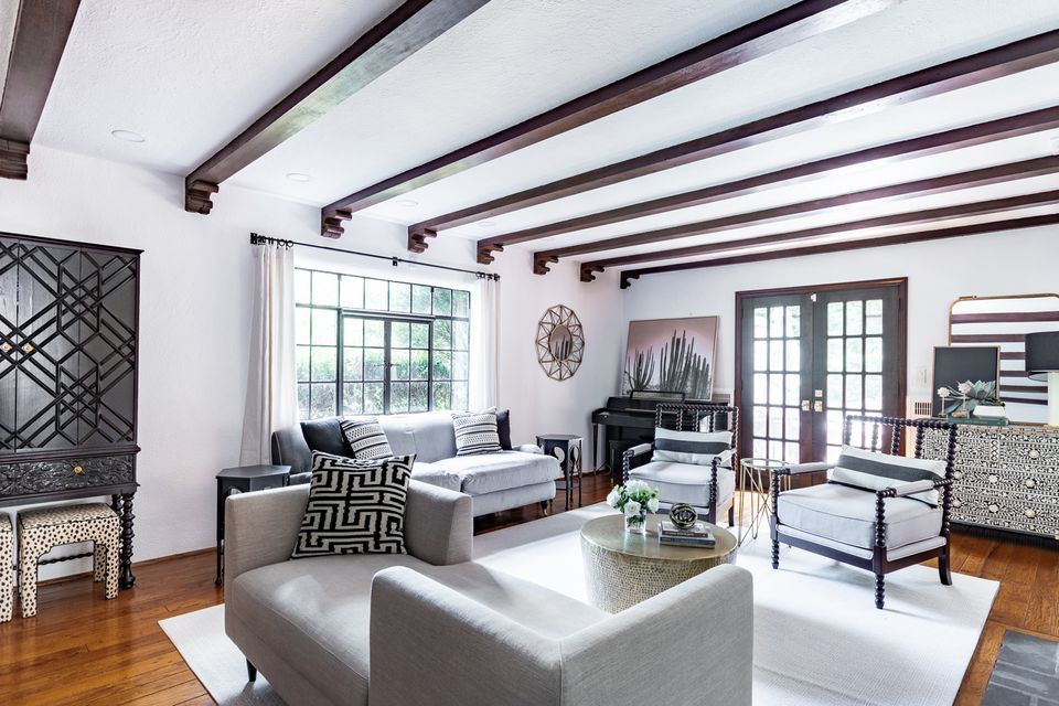 a neutral living room with several dark wood beams and caramel wood floors
