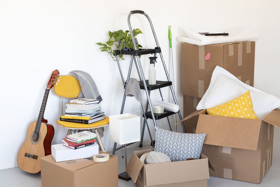 Cardboard boxes for moving with a step ladder, chair and guitar