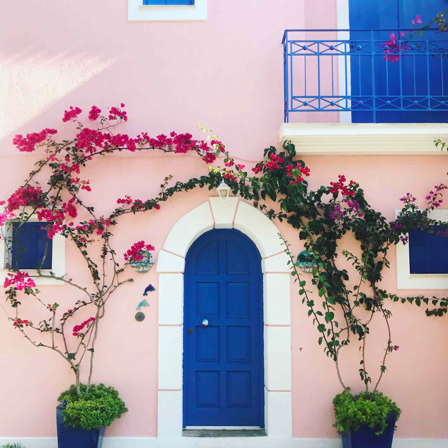 A pink house with a blue door in Greece