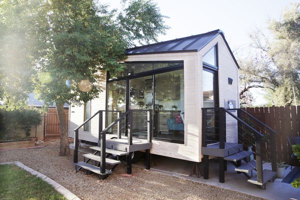A tiny house with large glass windows, sits in the backyard, surrounded by a wooden fence and trees.