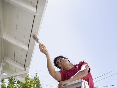 A man painting house eaves