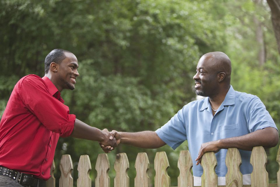 Neighbors greeting each other over a fence